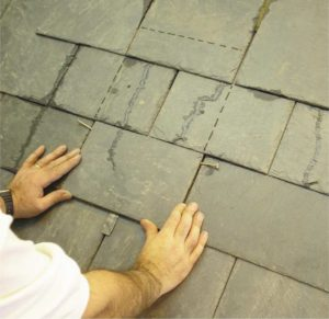 Slide the slate into position (nails used as a pivot to lift the head).